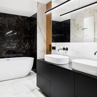 Inspiration for a mid-sized contemporary bathroom in Tampa with flat-panel cabinets, black cabinets, a freestanding tub, black and white tile, marble, white walls, marble floors, a vessel sink, white floor, a niche, a double vanity, a built-in vanity and wood walls.