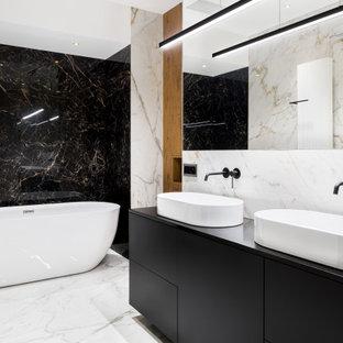 Свежая идея для дизайна: ванная комната среднего размера в современном стиле с плоскими фасадами, черными фасадами, отдельно стоящей ванной, черно-белой плиткой, мраморной плиткой, белыми стенами, мраморным полом, настольной раковиной, белым полом, нишей, тумбой под две раковины, встроенной тумбой и деревянными стенами - отличное фото интерьера
