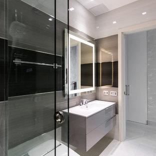 Idee per una stanza da bagno design di medie dimensioni con ante lisce, ante grigie, doccia alcova, WC monopezzo, piastrelle nere, piastrelle marroni, piastrelle grigie, piastrelle di vetro, pavimento in gres porcellanato, lavabo integrato e top in vetro