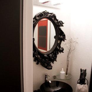 Imagen de cuarto de baño bohemio, pequeño, con lavabo sobreencimera, puertas de armario negras, encimera de vidrio, sanitario de una pieza, baldosas y/o azulejos negros, baldosas y/o azulejos de cerámica, paredes blancas y suelo de baldosas de cerámica