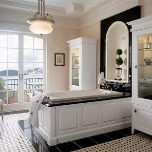 Inspiration pour une grand salle de bain principale traditionnelle avec un placard avec porte à panneau surélevé, des portes de placard blanches, une baignoire posée, un carrelage noir et blanc, des carreaux de céramique, un mur beige, un sol en carrelage de céramique et un plan de toilette en onyx.