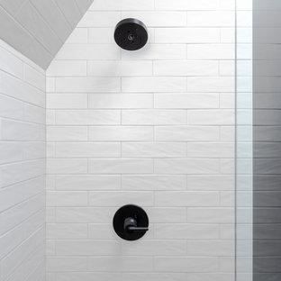 Modelo de cuarto de baño con ducha, urbano, de tamaño medio, con ducha empotrada, sanitario de una pieza, suelo de azulejos de cemento, ducha abierta, armarios con paneles empotrados, puertas de armario negras, baldosas y/o azulejos grises, baldosas y/o azulejos de cemento, paredes negras, lavabo integrado, encimera de acrílico, suelo negro y encimeras blancas
