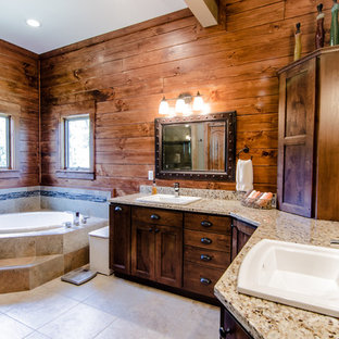 Example of a mountain style drop-in bathtub design in Other with a drop-in sink, recessed-panel cabinets and dark wood cabinets