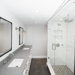 ニューヨークの中くらいのトランジショナルスタイルのおしゃれなマスターバスルーム (シェーカースタイル扉のキャビネット、白いキャビネット、ダブルシャワー、ビデ、白いタイル、セラミックタイル、グレーの壁、セメントタイルの床、オーバーカウンターシンク、クオーツストーンの洗面台、黒い床、開き戸のシャワー) の写真