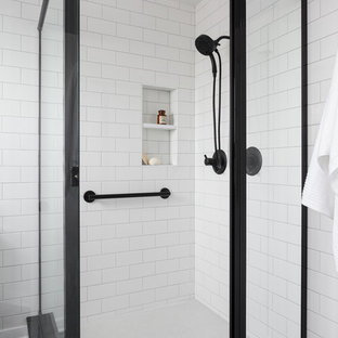 Example of a mid-sized transitional master black and white tile and ceramic tile porcelain floor and black floor corner shower design in Seattle with shaker cabinets, medium tone wood cabinets, a one-piece toilet, gray walls, an undermount sink, quartz countertops and a hinged shower door