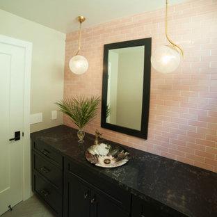 Idee per una stanza da bagno stile marino di medie dimensioni con ante in stile shaker, ante nere, WC monopezzo, piastrelle rosa, piastrelle in ceramica, pareti beige, pavimento in gres porcellanato, lavabo a bacinella, top in quarzo composito, pavimento grigio e top nero