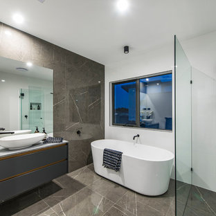 Contemporary master bathroom in Canberra - Queanbeyan with flat-panel cabinets, grey cabinets, a freestanding tub, a curbless shower, gray tile, white walls, a vessel sink and grey floor.