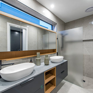 Inspiration for a contemporary bathroom in Canberra - Queanbeyan with flat-panel cabinets, grey cabinets, a curbless shower, gray tile, grey walls, a vessel sink and grey floor.