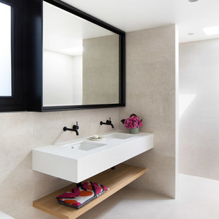 Inspiration for a contemporary bathroom in Melbourne with a curbless shower, a wall-mount toilet, beige tile, beige walls, an undermount sink, beige floor, an open shower and white benchtops.