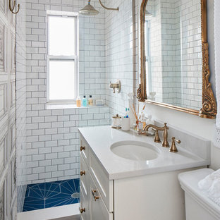 Small eclectic 3/4 white tile and ceramic tile ceramic floor and blue floor bathroom photo in New York with shaker cabinets, white cabinets, a two-piece toilet, white walls, an undermount sink, engineered quartz countertops and gray countertops