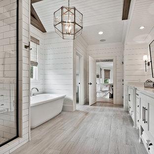 Foto på ett stort amerikanskt vit en-suite badrum, med luckor med upphöjd panel, vita skåp, ett fristående badkar, en dusch i en alkov, en toalettstol med separat cisternkåpa, vit kakel, porslinskakel, vita väggar, klinkergolv i keramik, ett undermonterad handfat, bänkskiva i kvarts, beiget golv och dusch med gångjärnsdörr