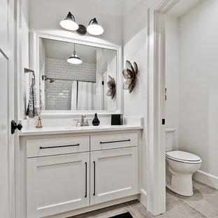 Exemple d'une grand salle de bain craftsman avec un placard avec porte à panneau surélevé, des portes de placard blanches, une baignoire encastrée, un combiné douche/baignoire, un WC séparé, un carrelage blanc, des carreaux de porcelaine, un mur blanc, un sol en carrelage de terre cuite, un lavabo encastré, un plan de toilette en quartz modifié, un sol gris, une cabine de douche à porte coulissante et un plan de toilette blanc.