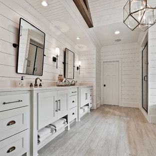 Bathroom - large craftsman master white tile and porcelain tile ceramic floor and beige floor bathroom idea in Other with raised-panel cabinets, white cabinets, a two-piece toilet, white walls, an undermount sink, engineered quartz countertops, a hinged shower door and white countertops