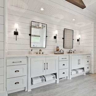他の地域の広いカントリー風おしゃれなマスターバスルーム (白いキャビネット、白い壁、セラミックタイルの床、アンダーカウンター洗面器、クオーツストーンの洗面台、白い洗面カウンター、シェーカースタイル扉のキャビネット、グレーの床) の写真