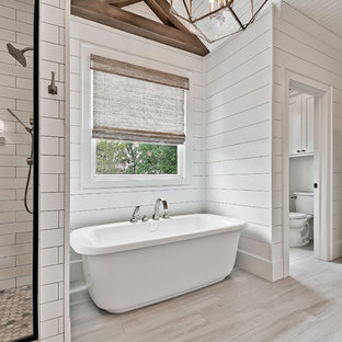 This is an example of a large country master bathroom in Other with a freestanding tub, an alcove shower, a two-piece toilet, white tile, porcelain tile, white walls, ceramic floors and grey floor.