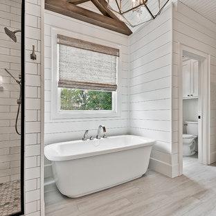 Bild på ett stort lantligt en-suite badrum, med ett fristående badkar, en dusch i en alkov, en toalettstol med separat cisternkåpa, vit kakel, porslinskakel, vita väggar, klinkergolv i keramik och grått golv