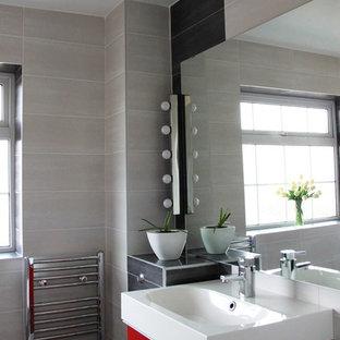 Exempel på ett litet modernt badrum för barn, med släta luckor, röda skåp, ett platsbyggt badkar, en dusch/badkar-kombination, en vägghängd toalettstol, grå kakel, cementkakel, grå väggar, klinkergolv i porslin, ett integrerad handfat och kaklad bänkskiva