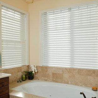 Esempio di una stanza da bagno tradizionale con ante lisce, ante in legno bruno, vasca sottopiano, piastrelle beige, piastrelle in travertino, pareti beige e top in laminato