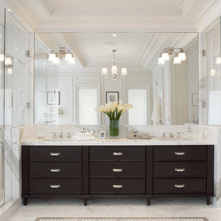 Example of a transitional master corner shower design in New York with recessed-panel cabinets, dark wood cabinets, a one-piece toilet, white walls and an undermount sink