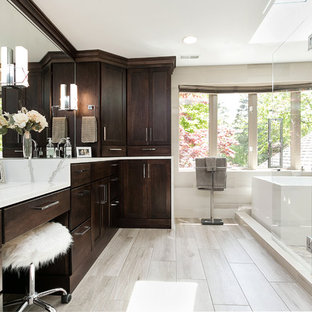 Freestanding bathtub - transitional master beige floor freestanding bathtub idea in Detroit with flat-panel cabinets, dark wood cabinets, beige walls, a hinged shower door and white countertops