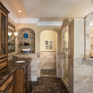 Новый формат декора квартиры: большая главная ванная комната в классическом стиле с врезной раковиной, бежевой плиткой, столешницей из известняка, отдельно стоящей ванной, бежевыми стенами, полом из известняка, фасадами цвета дерева среднего тона, душем в нише, стеклянными фасадами, плиткой из известняка, коричневой столешницей, раздельным унитазом, коричневым полом и душем с распашными дверями