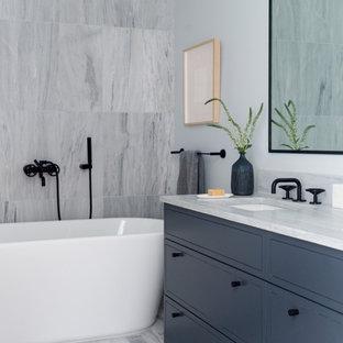 Immagine di una stanza da bagno minimalista con ante lisce, ante grigie, vasca freestanding, piastrelle grigie, pareti grigie, lavabo sottopiano, pavimento grigio, top grigio e mobile bagno incassato