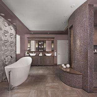 Пример оригинального дизайна: огромная главная ванная комната в современном стиле с плоскими фасадами, фасадами цвета дерева среднего тона, отдельно стоящей ванной, унитазом-моноблоком, коричневой плиткой, керамогранитной плиткой, фиолетовыми стенами, полом из керамогранита, настольной раковиной, столешницей из искусственного кварца, серым полом, душем с распашными дверями и серой столешницей
