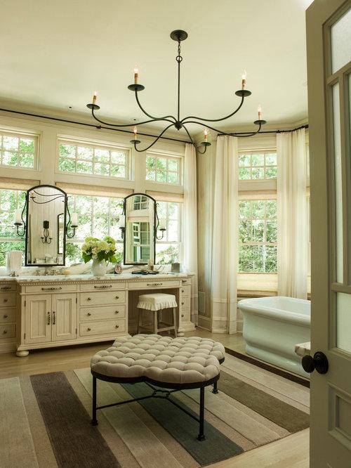 shabbychic style master bathtub idea in miami with beige cabinets