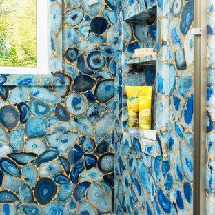 Bild på ett mellanstort eklektiskt badrum för barn, med släta luckor, skåp i mörkt trä, ett platsbyggt badkar, en dusch/badkar-kombination, en toalettstol med hel cisternkåpa, blå kakel, stenhäll, vita väggar, klinkergolv i porslin, ett fristående handfat, vitt golv och dusch med skjutdörr