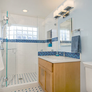 サンフランシスコの中サイズのトラディショナルスタイルのおしゃれな子供用バスルーム (シェーカースタイル扉のキャビネット、茶色いキャビネット、アルコーブ型シャワー、分離型トイレ、青いタイル、磁器タイル、青い壁、磁器タイルの床、アンダーカウンター洗面器、珪岩の洗面台、マルチカラーの床、開き戸のシャワー、ベージュのカウンター) の写真
