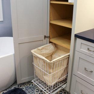 Inredning av ett klassiskt mellanstort blå blått en-suite badrum, med släta luckor, grå skåp, ett fristående badkar, en hörndusch, en toalettstol med separat cisternkåpa, grå kakel, tunnelbanekakel, grå väggar, kalkstensgolv, ett undermonterad handfat, bänkskiva i kvarts, blått golv och dusch med gångjärnsdörr