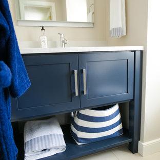 Modelo de cuarto de baño infantil, clásico renovado, de tamaño medio, con suelo de baldosas de cerámica, lavabo bajoencimera, encimeras blancas, armarios abiertos, puertas de armario azules, encimera de cuarzo compacto y suelo blanco