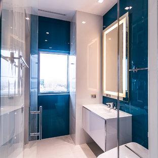 Immagine di una stanza da bagno padronale design di medie dimensioni con ante lisce, ante bianche, doccia alcova, WC monopezzo, piastrelle blu, piastrelle bianche, pareti blu, pavimento in gres porcellanato, lavabo integrato, piastrelle in ceramica e top in vetro