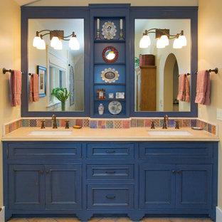 サンフランシスコの中くらいのサンタフェスタイルのおしゃれなマスターバスルーム (インセット扉のキャビネット、青いキャビネット、ベージュの壁、アルコーブ型シャワー、マルチカラーのタイル、磁器タイル、テラコッタタイルの床、アンダーカウンター洗面器、人工大理石カウンター、ベージュの床、開き戸のシャワー) の写真