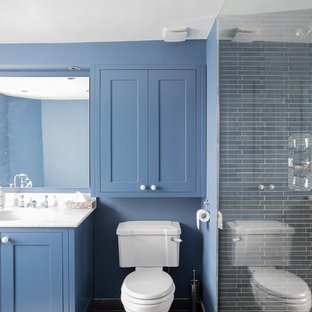 Design ideas for a large contemporary family bathroom in London with shaker cabinets, blue cabinets, a corner bath, a walk-in shower, a two-piece toilet, black tiles, slate tiles, blue walls, slate flooring, a submerged sink, marble worktops, grey floors, an open shower and white worktops.