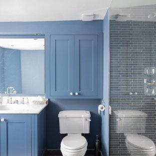 Diseño de cuarto de baño infantil, contemporáneo, grande, con armarios estilo shaker, puertas de armario azules, bañera esquinera, ducha abierta, sanitario de dos piezas, baldosas y/o azulejos negros, baldosas y/o azulejos de pizarra, paredes azules, suelo de pizarra, lavabo bajoencimera, encimera de mármol, suelo gris, ducha abierta y encimeras blancas