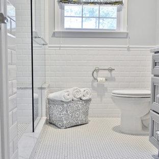 Modelo de cuarto de baño principal, tradicional, pequeño, con armarios con paneles empotrados, encimera de mármol, ducha empotrada, baldosas y/o azulejos blancos, baldosas y/o azulejos de porcelana, paredes grises y suelo con mosaicos de baldosas