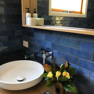 他の地域の中くらいのコンテンポラリースタイルのおしゃれなマスターバスルーム (フラットパネル扉のキャビネット、淡色木目調キャビネット、オープン型シャワー、分離型トイレ、青いタイル、セラミックタイル、青い壁、セラミックタイルの床、ベッセル式洗面器、木製洗面台、グレーの床、オープンシャワー、ベージュのカウンター) の写真
