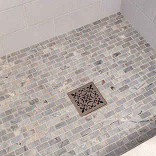 Alcove shower - small traditional master blue tile and ceramic tile porcelain floor and gray floor alcove shower idea in Seattle with raised-panel cabinets, gray cabinets, a one-piece toilet, gray walls, an undermount sink, engineered quartz countertops and a hinged shower door