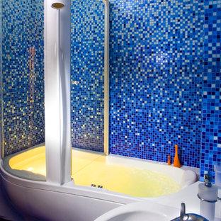 Ejemplo de cuarto de baño infantil, contemporáneo, de tamaño medio, con armarios tipo mueble, puertas de armario blancas, bañera empotrada, combinación de ducha y bañera, sanitario de pared, baldosas y/o azulejos azules, baldosas y/o azulejos en mosaico, paredes azules, suelo con mosaicos de baldosas y lavabo integrado