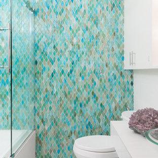 Aménagement d'une petit salle de bain classique pour enfant avec un placard à porte plane, des portes de placard blanches, une baignoire en alcôve, un combiné douche/baignoire, un WC séparé, un carrelage bleu, un carrelage en pâte de verre, un mur blanc, un sol en carrelage de porcelaine, une vasque, un plan de toilette en carrelage, un sol blanc, une cabine de douche à porte coulissante, un plan de toilette blanc, une niche, meuble simple vasque, meuble-lavabo suspendu et boiseries.