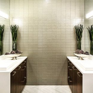 Trendy master beige tile and glass tile porcelain floor and beige floor bathroom photo in Omaha with flat-panel cabinets, dark wood cabinets, a vessel sink, solid surface countertops and white countertops