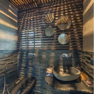 Foto de cuarto de baño rural, pequeño, con sanitario de pared, baldosas y/o azulejos de piedra, paredes grises, suelo de cemento, lavabo sobreencimera y suelo negro