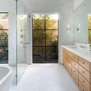 Inredning av ett modernt stort vit vitt en-suite badrum, med släta luckor, skåp i mellenmörkt trä, ett fristående badkar, en kantlös dusch, vit kakel, vita väggar, ett undermonterad handfat, vitt golv, dusch med gångjärnsdörr, marmorkakel, marmorgolv och bänkskiva i akrylsten