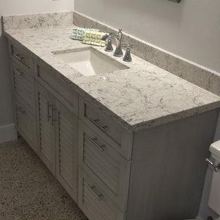 他の地域のビーチスタイルのおしゃれな浴室 (ルーバー扉のキャビネット、グレーのキャビネット、テラゾーの床、クオーツストーンの洗面台、グレーの床) の写真