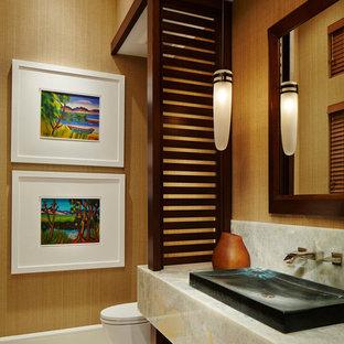 Diseño de cuarto de baño con ducha, actual, de tamaño medio, con lavabo sobreencimera, encimera de ónix, sanitario de una pieza, paredes amarillas y suelo de piedra caliza