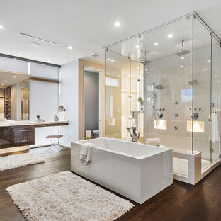 Design ideas for a large contemporary master bathroom in Miami with flat-panel cabinets, dark wood cabinets, a freestanding tub, a double shower, onyx benchtops, brown floor, a hinged shower door, white benchtops, white tile, grey walls and dark hardwood floors.