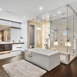 Пример оригинального дизайна: большая главная ванная комната в современном стиле с плоскими фасадами, темными деревянными фасадами, отдельно стоящей ванной, двойным душем, столешницей из оникса, коричневым полом, душем с распашными дверями, белой столешницей, белой плиткой, серыми стенами и темным паркетным полом