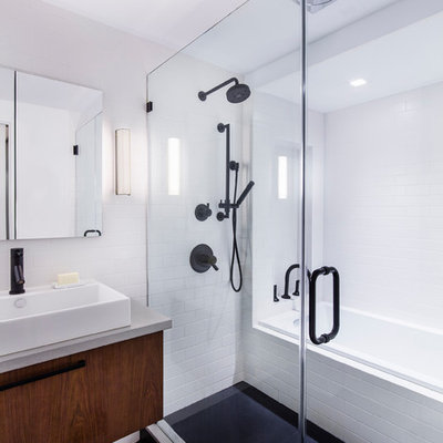 Inspiration for a mid-sized modern master white tile and subway tile porcelain tile bathroom remodel in New York with a vessel sink, flat-panel cabinets, dark wood cabinets, concrete countertops, a wall-mount toilet and white walls