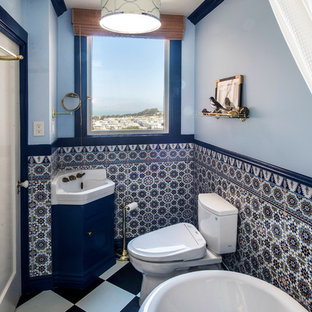 Foto de cuarto de baño con ducha, clásico, grande, con bañera con patas, paredes azules, armarios estilo shaker, puertas de armario azules, sanitario de dos piezas, baldosas y/o azulejos azules, baldosas y/o azulejos multicolor, baldosas y/o azulejos de cerámica, lavabo encastrado, encimeras blancas, suelo vinílico y suelo multicolor
